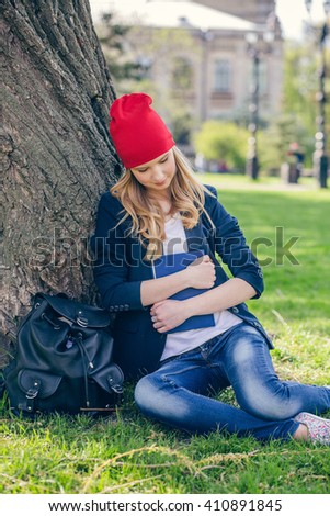 Beautiful and happy young student girl in red hat holding book sitting on green grass under the tree near the campus, university buildings, school, education. Summer or spring green park