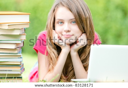 beautiful and happy young student girl lying on grass with laptop computer, smiling and looking into the camera. Pile of books nearby Summer or spring green park in background - stock photo