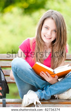 beautiful and happy young student girl sitting on bench, holding book in her hands, smiling and looking into the camera. Summer or spring green park in background