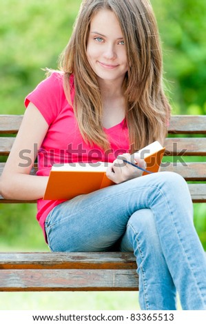 beautiful and happy young student girl sitting on bench, holding book in her hands, smiling and looking into the camera. Summer or spring green park in background - stock photo