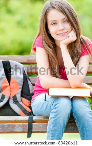 beautiful and happy young student girl sitting on bench with book, smiling and looking into the camera. Summer or spring green park in background - stock photo