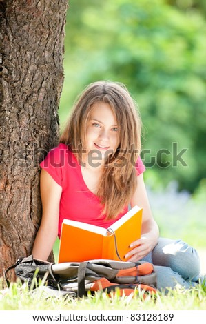beautiful and happy young student girl sitting on green grass under the tree, smiling and reading book, looking into the camera. Summer or spring green park in background