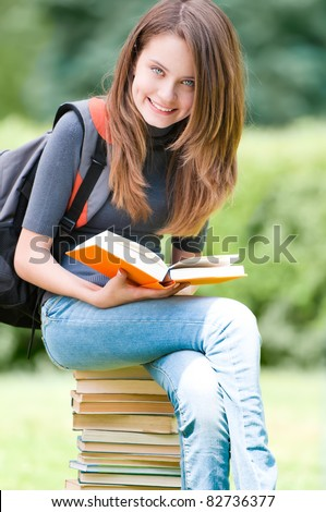 beautiful and happy young student girl sitting on pile of books, holding book in her hands, smiling and looking into the camera. Backpack on her shoulder. Summer or spring green park in background - stock photo