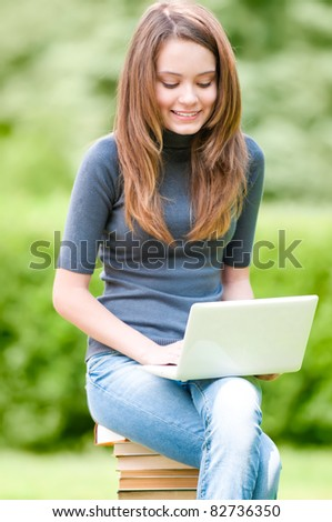 beautiful and happy young student girl sitting on pile of books, smiling and working on laptop computer. Summer or spring green park in background - stock photo