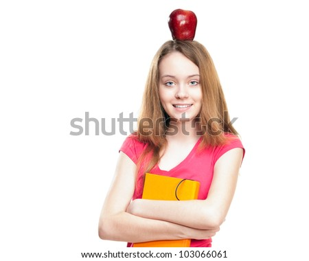 Beautiful and happy young student girl with apple on her head and book in her hands. Looking into the camera. Isolated on white background. - stock photo