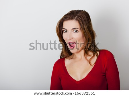 Beautiful and happy young woman against a gray wall