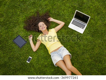 Beautiful and happy young woman lying on the grass surrounded by technology devices - stock photo