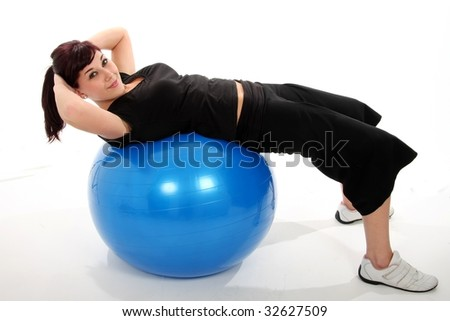 Beautiful and healthy fitness girl lying on a blue exercise ball