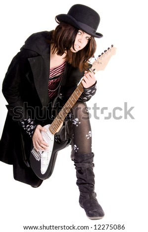 Beautiful and hip scene girl with red and black hair in a pink striped off the shoulder top, pirate sleeves and a felt bowler kneeling and playing an electric guitar