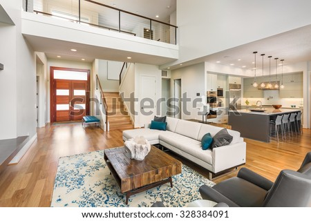 Beautiful and large living room interior with hardwood floors and vaulted ceiling in new luxury home. View of Kitchen, entryway, and second story loft style area - stock photo