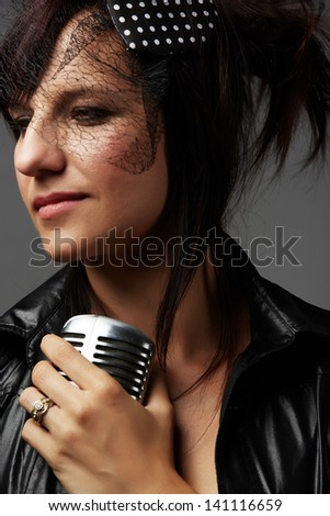 Beautiful and mature adult caucasian woman with red lips, dark hair and brown eyes wearing a black leather jacket and holding a microphone