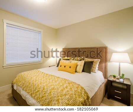 Beautiful and modern yellow bedroom in a home hotel. Interior design. - stock photo