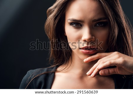 Beautiful and mysterious. Beautiful young woman touching her chin while standing against black background - stock photo