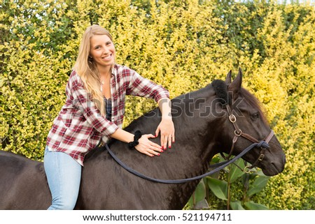Beautiful and natural young woman spending sometime with her horse