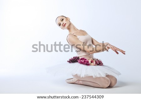 beautiful and plastic ballerina in tutu sitting on the floor, a ballet performance - stock photo