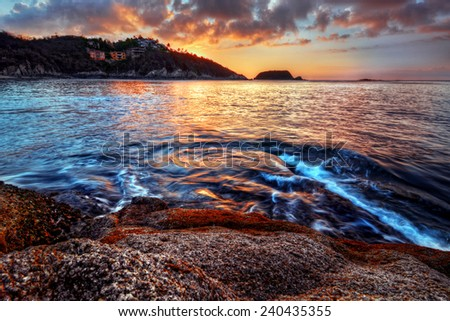 Beautiful and romantic sunset with distant cliffs and swirling waters - stock photo