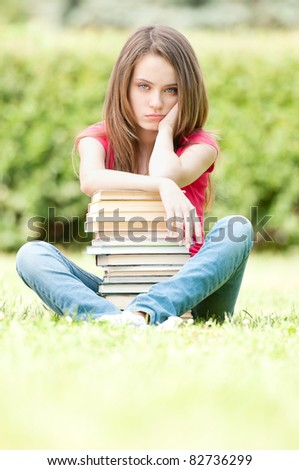 beautiful and sad young student girl sitting on green grass, pile of books under her hands. She is depressed and looking into the camera. Summer or spring green park in background - stock photo