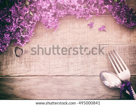 Beautiful and scented Purple Lavender Flowers place Setting with fork and spoon on Rustic Wood Background. Horizontal card with top down view and vintage retro tone cross processed with light effects