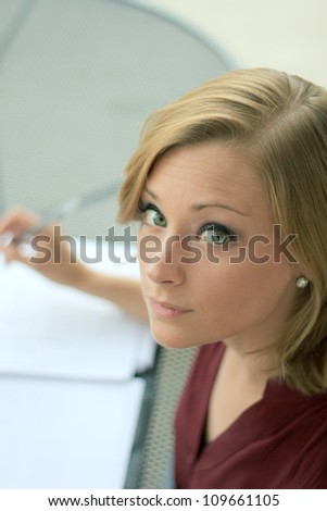 Beautiful and Serious Business Woman Looking At Camera While Writing - stock photo