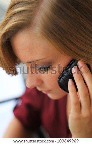 Beautiful and Serious Business Woman Talking on the Phone While Looking Down - stock photo