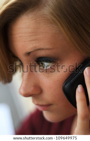 Beautiful and Serious Business Woman Talking on the Phone While Looking Straight Ahead - stock photo