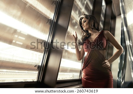 Beautiful and sexy adult brunette woman in elegance dress on luxury apartment  - stock photo