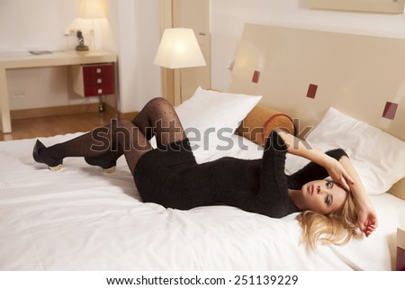 Beautiful and sexy attractive sensuality pretty young adult blonde woman wearing elegance fashionable black dress lying on the bed in bedroom luxury style hotel apartment - stock photo