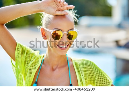 Beautiful and sexy blond girl in bikini and sunglasses - stock photo