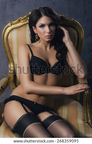 Beautiful and sexy girl in underwear sitting in a vintage armchair and posing.