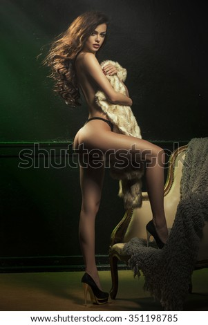 Beautiful and sexy girl with fur on a vintage armchair and posing.  - stock photo