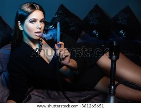 Beautiful and sexy glamorous woman smoking hookah - stock photo