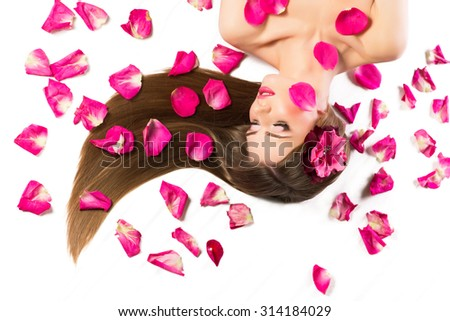 Beautiful and sexy model with rose petals, isolated on white background. - stock photo