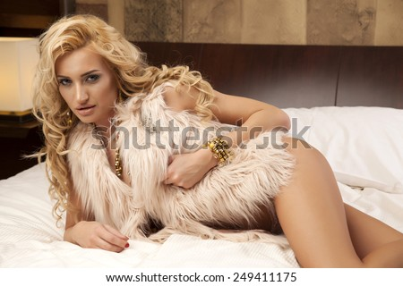 Beautiful and sexy sensuality young adult blonde woman wearing elegance fashionable fur and gold jewelry on the bed in luxury style apartment - stock photo