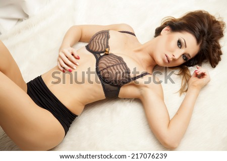 Beautiful and sexy young adult sensuality brunette woman in black lingerie on the white fur on luxury apartment - stock photo