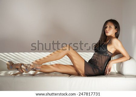 Beautiful and sexy young adult sensuality brunette woman in black lingerie on the white sofa on luxury apartment - stock photo