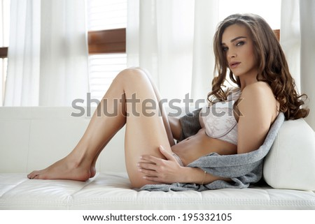 Beautiful and sexy young adult sensuality brunette woman in white lingerie and grey sweater on the white sofa in window on luxury apartment - stock photo
