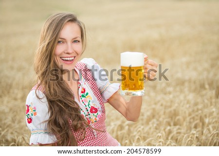 Beautiful and sexy young blond woman drinking beer in wheat field. soft daylight - stock photo