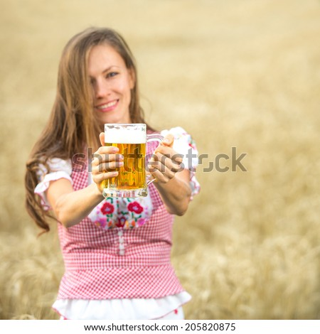 Beautiful and sexy young blond woman holding glass of beer. focus on glass and hands