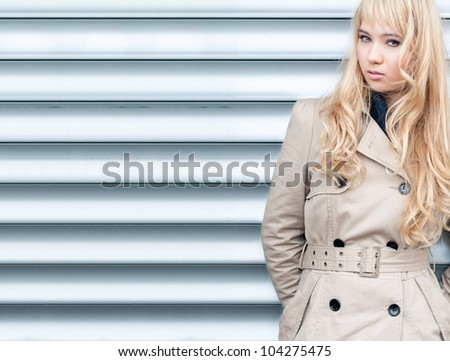 Beautiful and sexy young girl posing outside against garage door. Looking into the camera. Blond long hair and fashion look. - stock photo