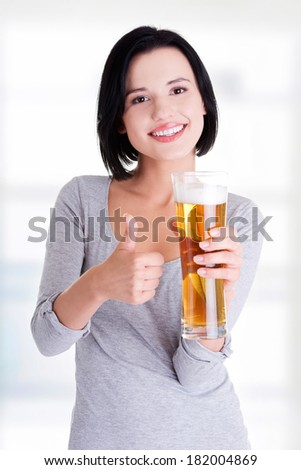 Beautiful and sexy young woman with glass of beer gesturing thumbs up - stock photo