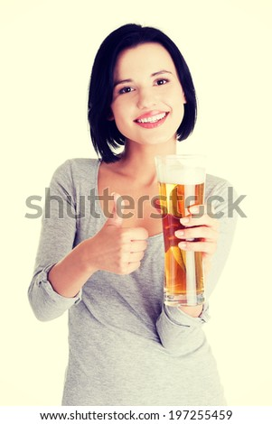 Beautiful and sexy young woman with glass of beer gesturing thumbs up