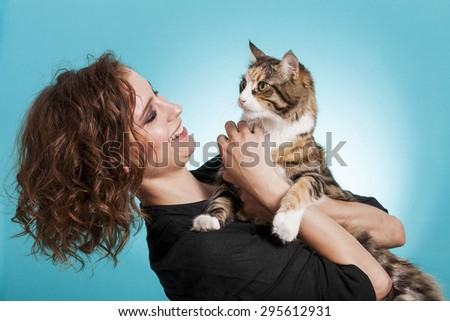 Beautiful and smiling girl holding cat - stock photo