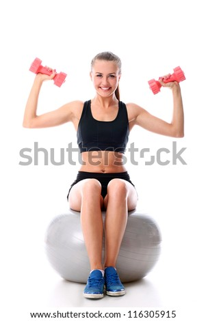 Beautiful and smiling woman doing exercises with dumbells on fitness ball over white background - stock photo