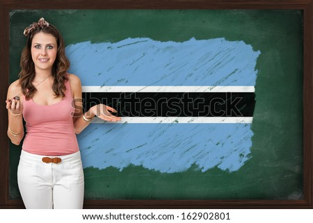 Beautiful and smiling woman showing flag of Botswana on blackboard, presentation for tourism and marketing research