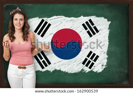 Beautiful and smiling woman showing flag of South Korea on blackboard, presentation for tourism and marketing research - stock photo
