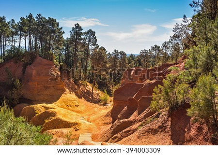 Beautiful and striking contrast between the green pine trees and yellow ocher soil. Unique red and orange hills in the province of Languedoc - Roussillon, France - stock photo