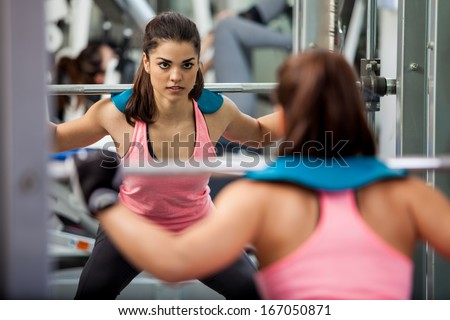 Beautiful and strong woman concentrated on her workout routine by doing squats with a barbell