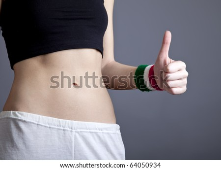 Beautiful and strong women's abs with metre show hand OK. Studio shot. - stock photo