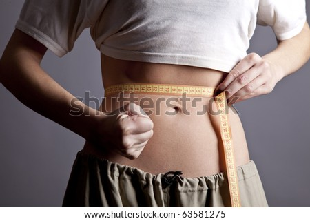 Beautiful and strong women's abs with metre. Studio shot. - stock photo