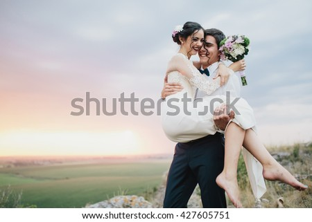Beautiful and stylish wedding couple on the background of sunset in the field.